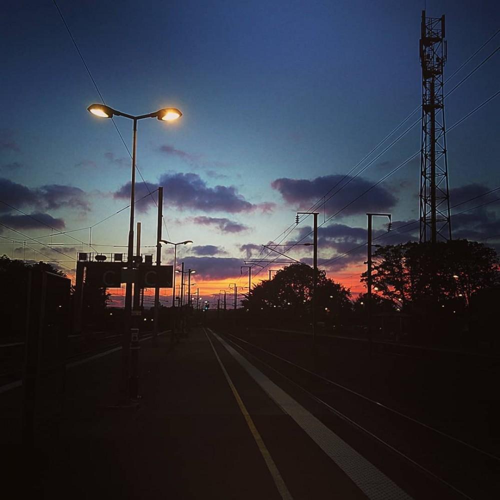 Coucher de soleil sur le quai d'une gare, avec un lampadaire allumé