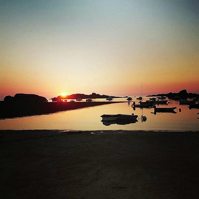 Photo du soleil qui se couche au loin, plage et bateaux